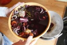 Giet de kip en groenten in wijn in een vergiet