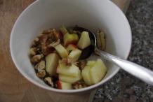 Verdeel de walnoten en appelstukjes over de ontbijtkommen