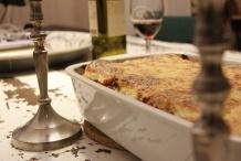 De lasagne op tafel met een goed glas wijn