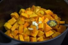 Doe pompoenblokjes, knoflook en de geraspte citroenschil in de pan